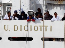 Migrants waits to disembark from Italian coast guard vessel 'Diciotti' as they arrive at the port of Catania