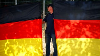 A man takes part in a protest against German Chancellor Angela Merkel as she visits the state parliament in Dresden