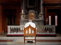 Pope Francis prays in front of a candle lit to remember victims of abuse by the church, inside St Mary's Pro Cathedral during his visit to Dublin