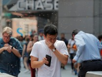 People react to a swarm of bees in Times Square in New York