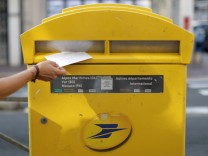 A woman puts a letter in a mailbox of French postal service company La Poste in Nice