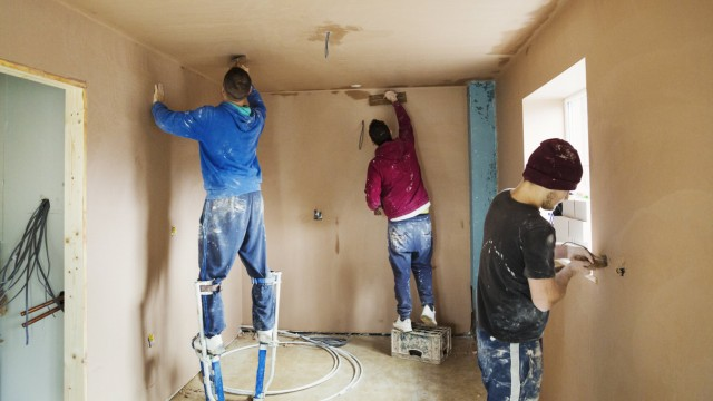 Three men two plasterers wearing stilts smoothing fresh plaster high up on the walls of a house und