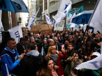 State workers gather during a protest against layoffs outside the Ministry of Justice in Buenos Aires' financial district