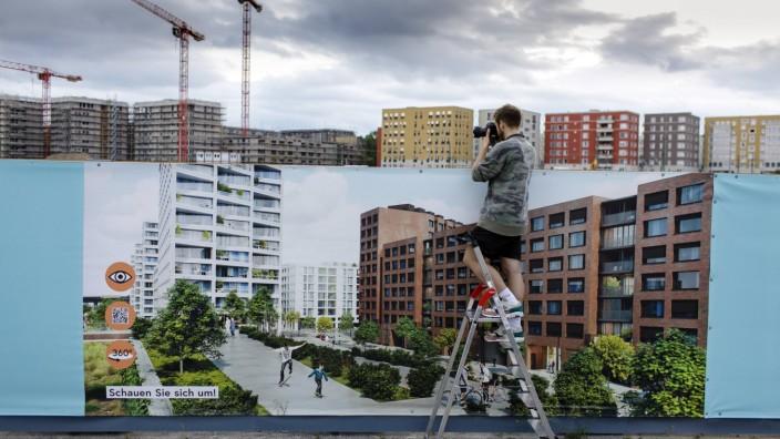 Ein Mann steht auf einer Leiter vor einer Informationswand zum Wohnungsbau und fotografiert eine Bau