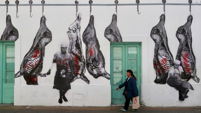 A woman walks outside a restaurant in Buenos Aires