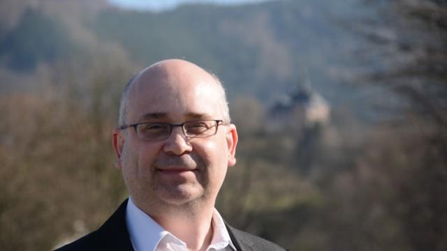 Immobilienmakler Matthias Helzel  aus Bruckmühl, im Hintergrund ein Schloss an der Saale