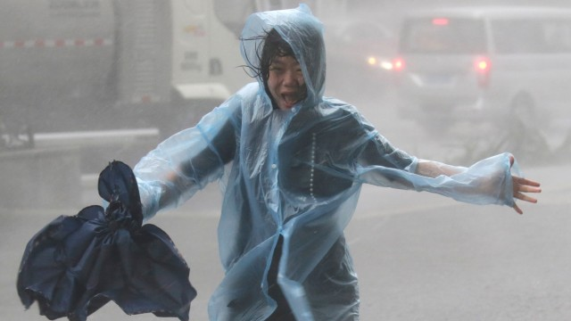 A woman runs in the rainstorm as Typhoon Mangkhut approaches in Shenzhen