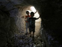 FILE PHOTO: Children walk in a makeshift shelter in an underground cave in Idlib