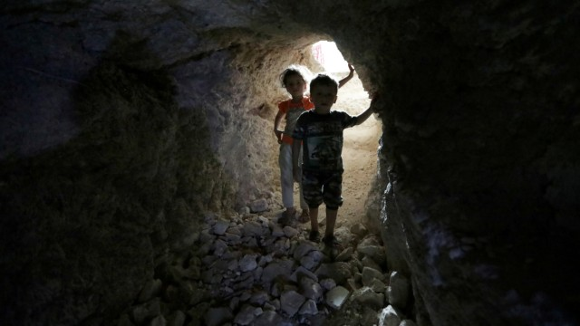 FILE PHOTO: Children walk in a makeshift shelter in an underground cave in Idlib