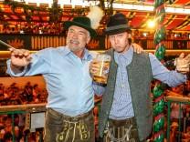 Arnold Schwarzenegger dirigiert die Kapelle im Marstall-Zelt auf dem Oktoberfest mit Sohn Patrick
