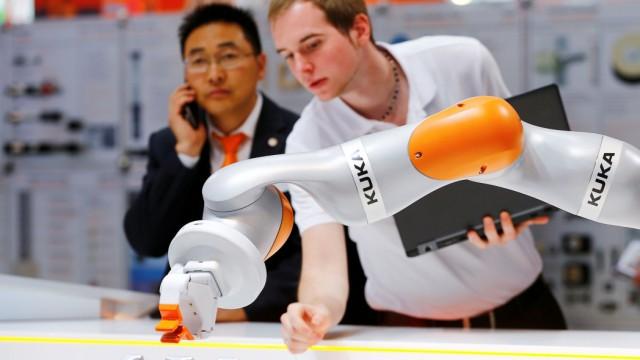 FILE PHOTO: A Kuka technician programs a robot arm of German industrial robot maker Kuka in Hanover