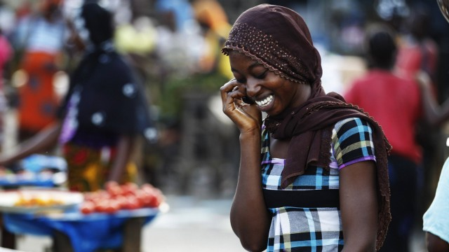 A woman talks on the phone at a market in Abidjan