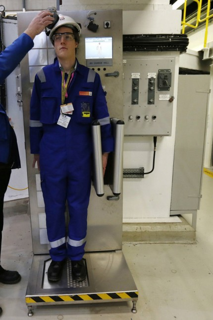 An environmental safety monitor scans an employee during a contamination checks in the charge hall inside EDF Energy's Hinkley Point B nuclear power station in Bridgwater, southwest England