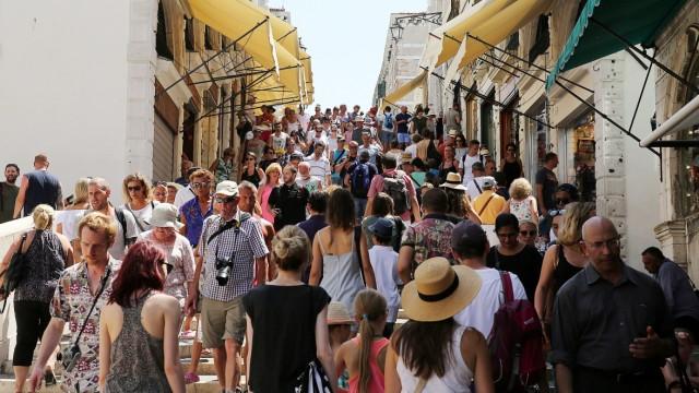 Touristen gehen über die Rialtobrücke in Venedig.