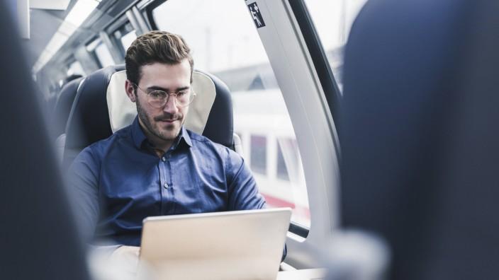 Ein Mann arbeitet im Zug. Viele Pendler nutzen die Fahrtzeit für den Job.