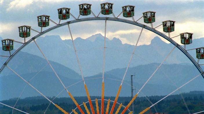 Das Riesenrad auf dem Oktoberfest mit Ausblick in die Alpen.