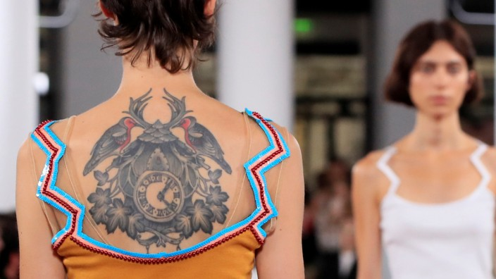 A model with a tattoo on her back presents a creation by designer Glenn Martens as part of his Spring/Summer 2019 women's ready-to-wear collection show for Y/Project during Paris Fashion Week