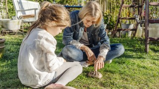 Smiling mature woman and girl with tortoise in garden Smiling mature woman and girl with tortoise in