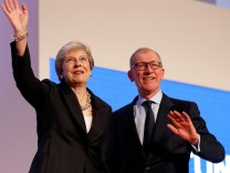 British Prime Minister Theresa May and her husband Philip acknowledge the applause after she delivered her keynote address on the final day of at the Conservative Party Conference in Birmingham