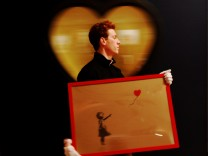 FILE PHOTO: An employee walks with artist Banksy's 'Girl and Balloon' 2009 signed and inscribed For Mike, past artist  Ryan Callanan's (known as RYCA) 'Mega Heart' 2011 at Bonhams auction house in London