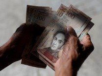 A man counts Venezuelan bolivar notes in downtown Caracas