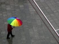 Mit buntem Regenschirm durchs graue Nass