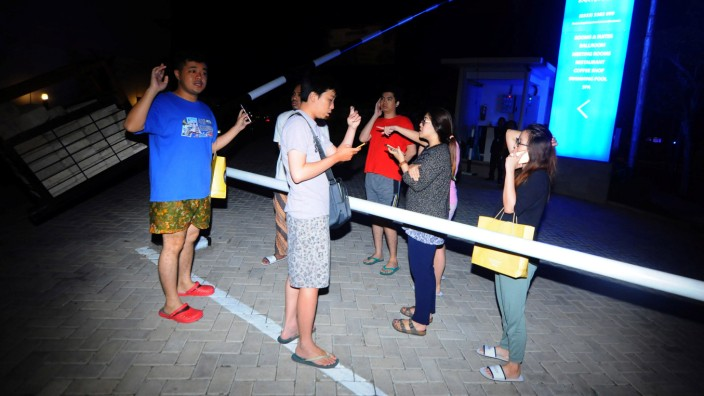 Hotel guests stand outside of a hotel shortly after an earthquake in Banyuwangi