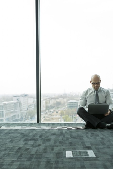 Businessman using laptop on empty office floor with cardboard box model released property released P