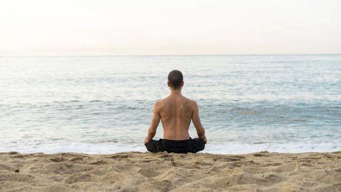 Spain Man doing yoga on the beach in the evening meditation rear view model released Symbolfoto P