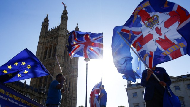 Anti-brexit protestors wave flags outside the Houses of Parliament in London