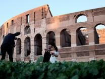 Ein Brautpaar wird vor dem Kolosseum in Rom fotografiert.