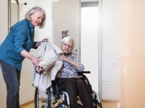 Woman taking care of old woman in wheelchair putting her jacket on model released Symbolfoto PUBLIC