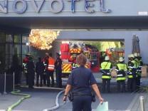 Feuerwehreinsatzkräfte nach dem Brand in einer Sauna im Novotel-Hotel in München.