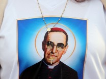 A faithful wears a t-shirt with the picture of El Salvador's Archbishop Oscar Romero before a mass for his canonisation at the Vatican
