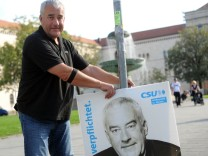 Ludwig Spaenle hängt eines seiner Plakate vom Landtagswahlkampf in München ab