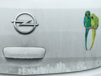 A sticker on an Opel car outside the car maker's factory is decorated with a sticker of two parrots in Ruesselsheim