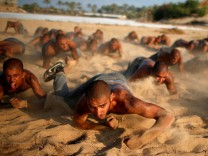 Palestinian cadets crawl as they demonstrate their skills at a police college run by the Hamas-led interior ministry, in Khan Younis