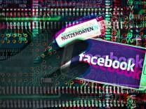 Schwarze Hand über Handy mit Facebook Schriftzug und USB Stick mit Aufschrift Nutzerdaten Symbolfot