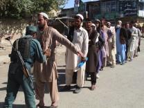 Ein Polizist kontrolliert Wähler in Afghanistan.