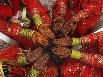 Muslim brides display hands painted with henna during a mass wedding ceremony in the western Indian city of Ahmedabad