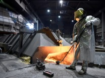 FILE PHOTO: A worker of German steel manufacturer Salzgitter AG stands in front of a furnace at a plant in Salzgitter