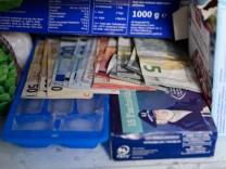 Geldscheine liegen in einem Tiefkühlfach