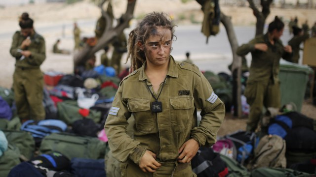 Israeli soldier of Caracal battalion stands next to backpacks after finishing march in Israel's Negev desert