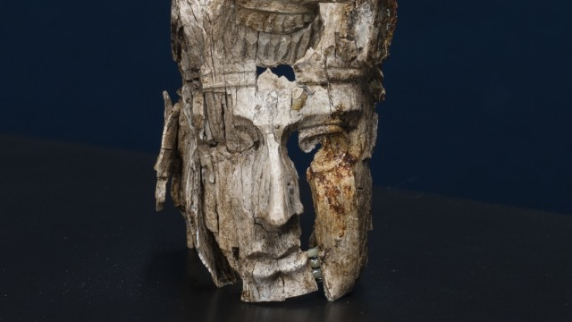 Ein original Kopffragment mit zersprungenen und durch den Brand verfärbten Stellen; Schnitzereien des Totenbettes von Haltern