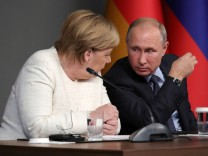 German Chancellor Angela Merkel and Russian President Vladimir Putin attend a news conference at the Syria summit in Istanbul