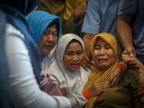 Indonesien - Trauernde Familienangehörige nach Flugzeugabsturz