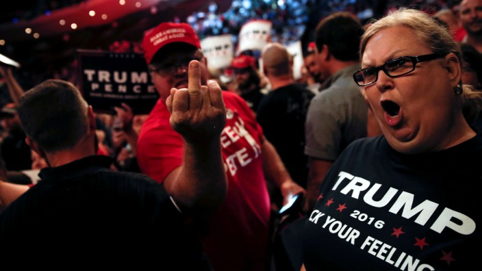 FILE PHOTO: Supporters of Republican U.S. presidential nominee Donald Trump scream and gesture at members of the media in a press area at a campaign rally in Cincinnati