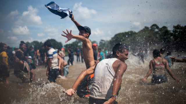 Migrants, part of a caravan from Central America en route to the United States, waves the colors of the Honduras flag as they celebrate after crossing into Mexico from Guatemala through the Suchiate River in Ciudad Hidalgo