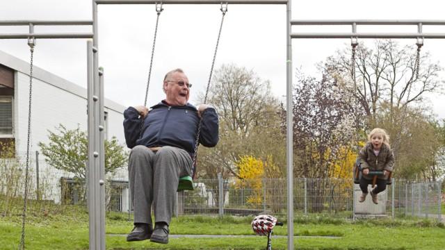 Großvater und die 3 jährige Enkeltochter schaukeln Großmutter steht daneben iblmpw03830879 jpg