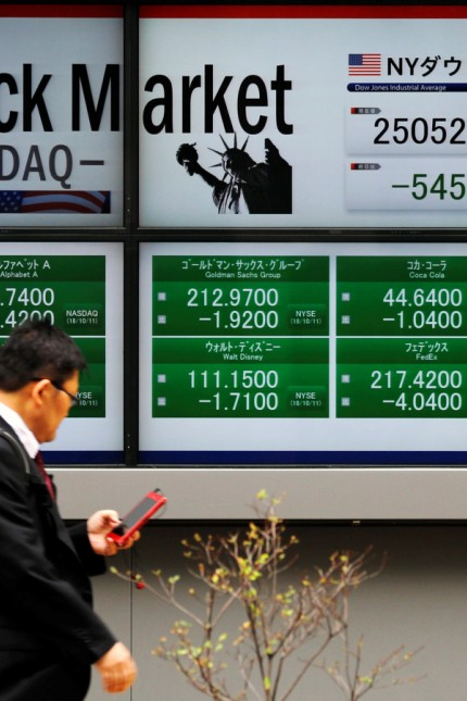 A man walks past electronic boards showing Dow Jones Industrial Average and and NASDAQ average in Tokyo